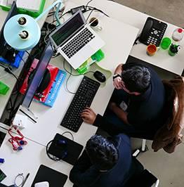 Dos jóvenes trabajan delante de un ordenador
