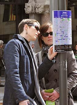 Dues dones miren un plànol situat al carrer
