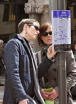Two women looking at a map located on the street